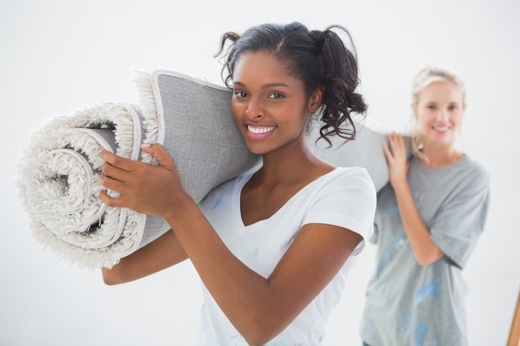 Young women carrying carpet.