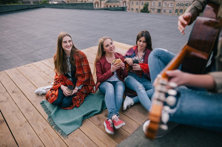 Young women listening to guitarist