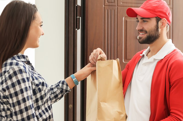 A woman receives a food order from a delivery driver
