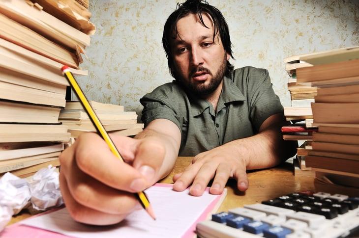 Man at desk working hard, sweating
