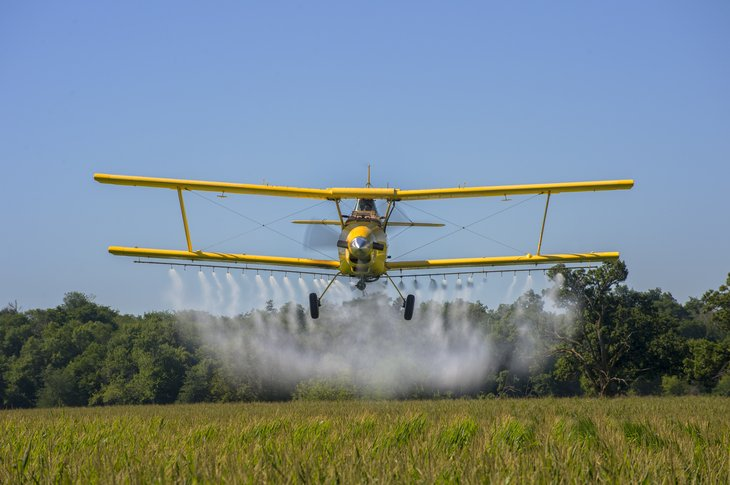 Crop duster over a farm in Iowa