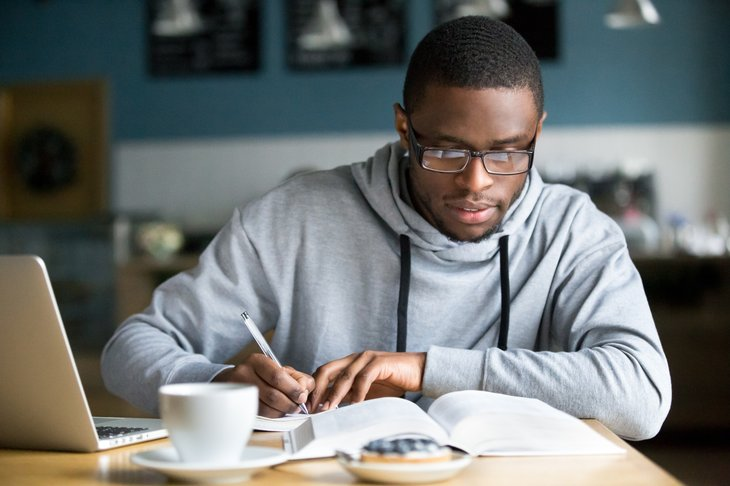 African American man writing at table.