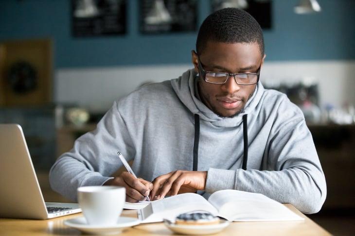 Hombre afroamericano escribiendo en la mesa.