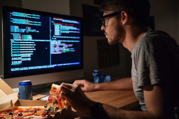 A computer programmer eats pizza while working at his desk