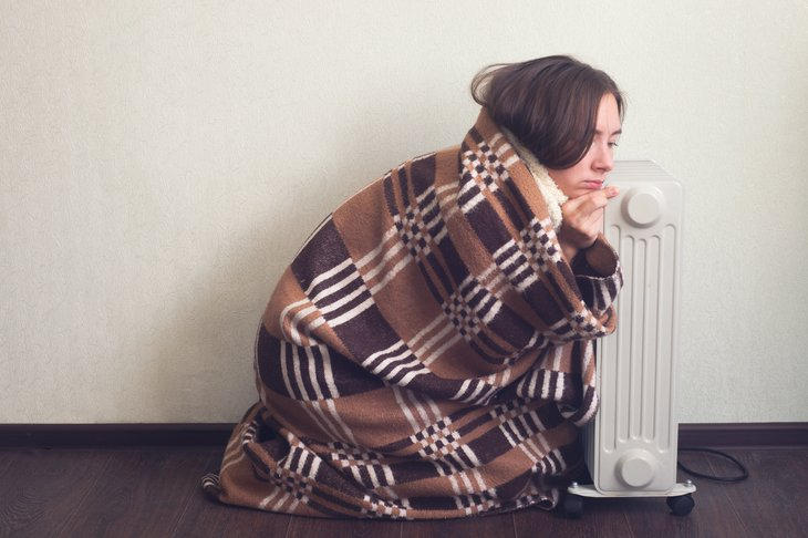 Cold young woman by electric heater