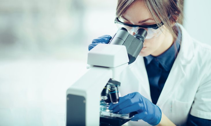 Female lab scientist using microscope