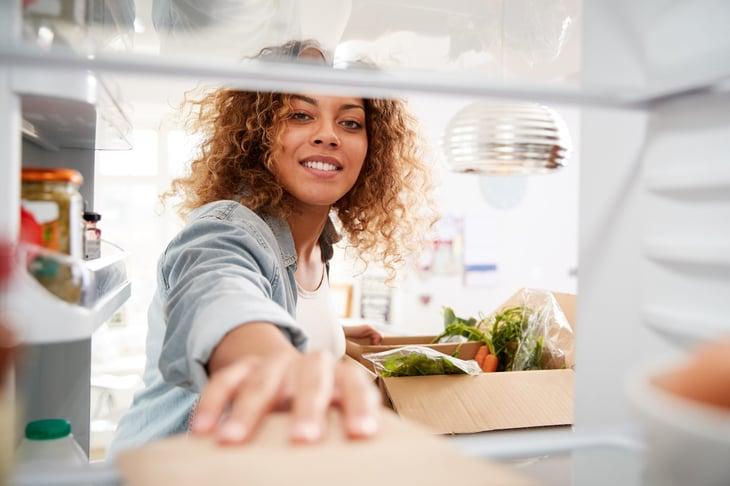 Woman reaching into her fridge