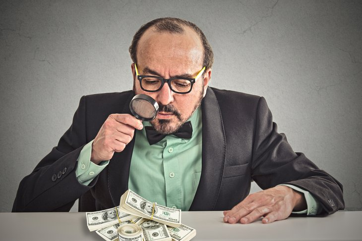 Businessman looking closely at pile of money