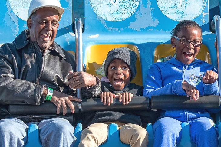 African American grandfather and kids on ride at the fair, Alabama