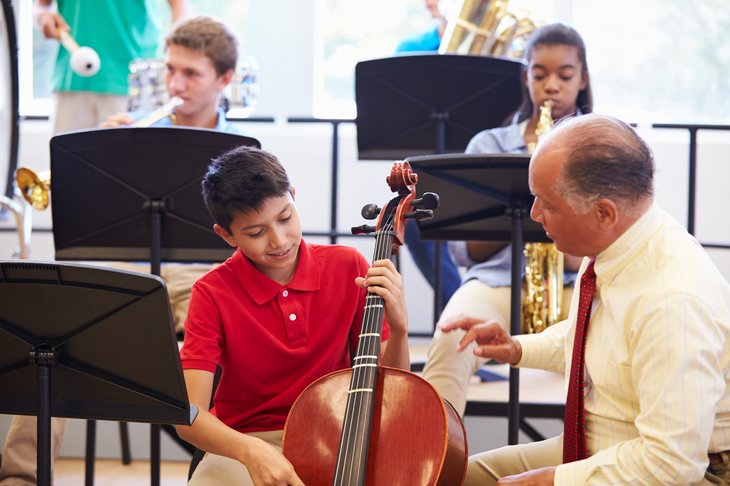 Students playing instruments with teacher in music class