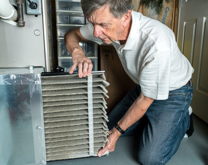 Senior man changing a folded dirty air filter in the HVAC furnace system in basement of home