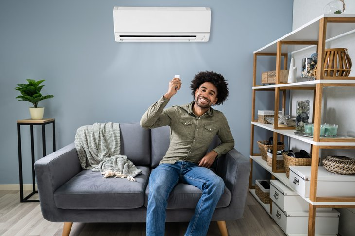 Young happy man sitting on couch operating air conditioner with remote control