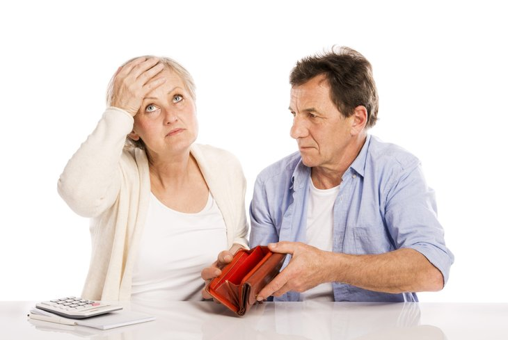 Senior couple with empty wallet discussing financial issues