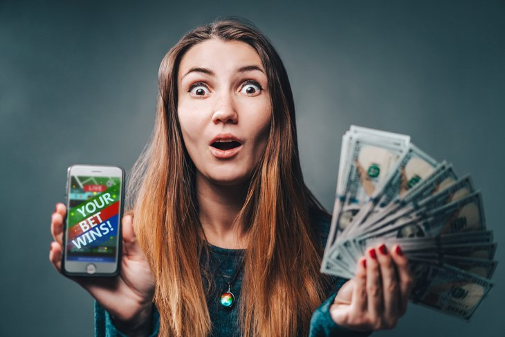 Surprised lottery winner holding cash