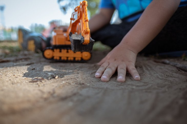 A child plays with a toy in dirt