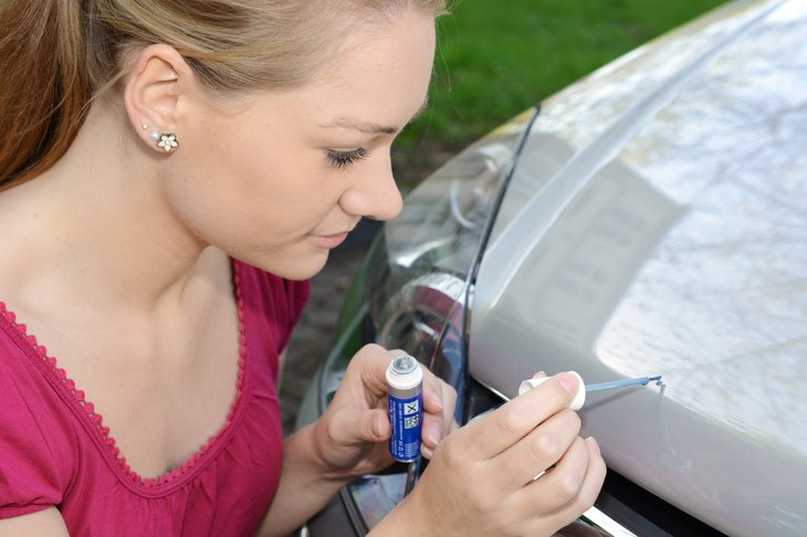 Woman repairs scratches and chips on car