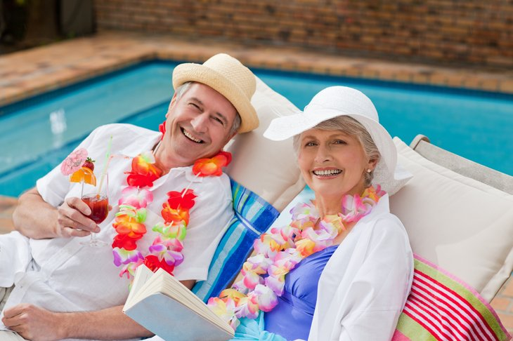 Older couple with leis sitting poolside