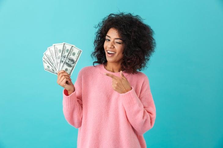 Happy woman holding cash