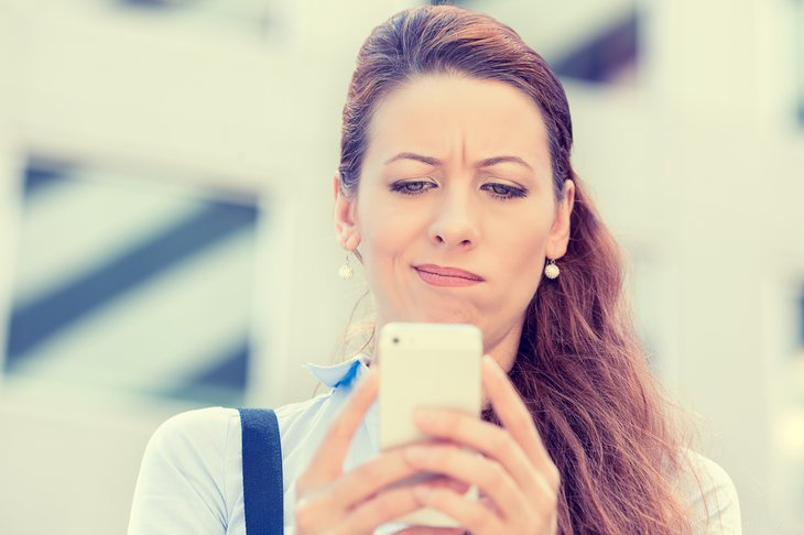 Woman looking skeptical on cellphone