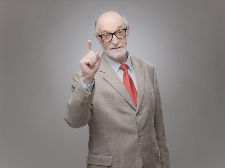 Senior man points finger up