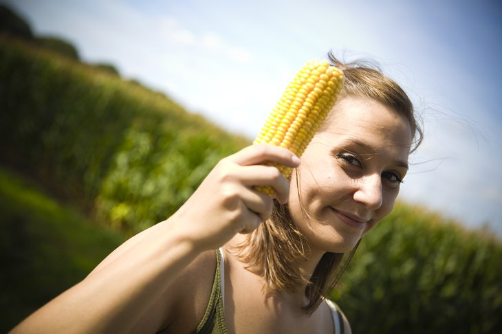 Woman holding an ear of corn