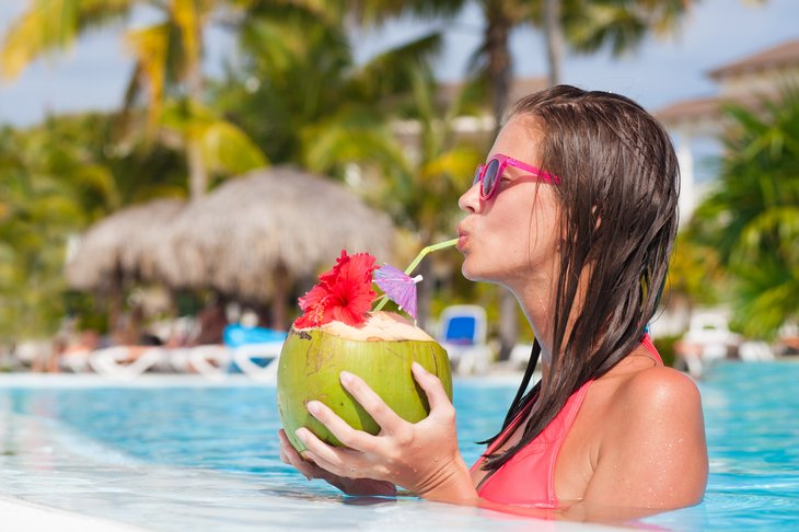 Woman sipping tropical drink in pool