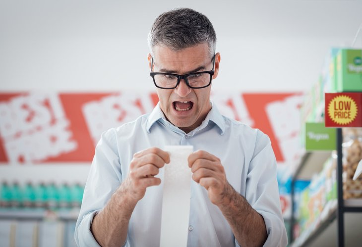 Unhappy man with grocery receipt