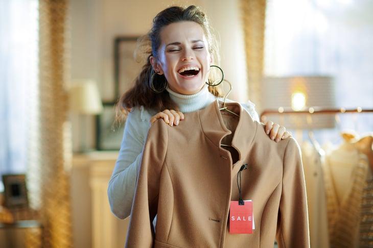 Happy shopper buying a coat on sale