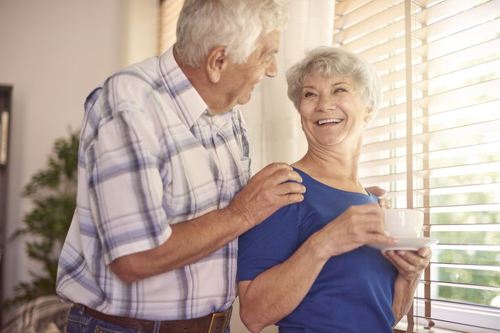 A senior couple drinks coffee and looks out a window of their home in the morning