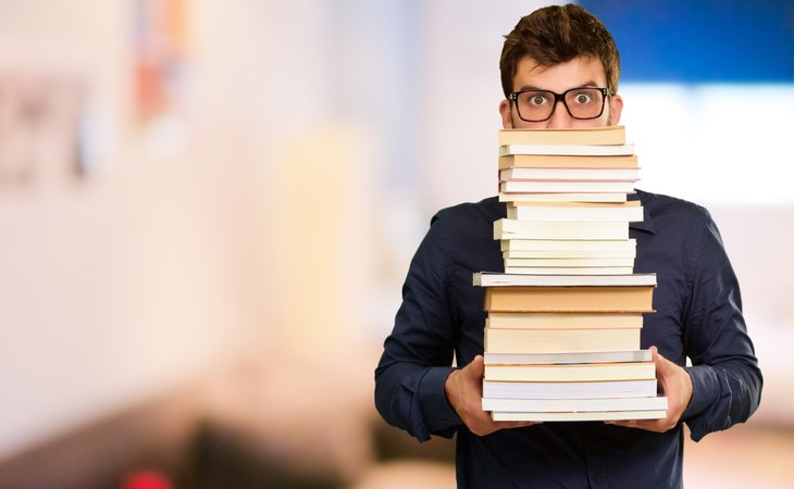 Young man with stack of books.