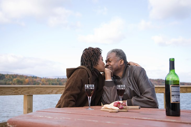 kissing retirees african american black ethnic older couple picnic