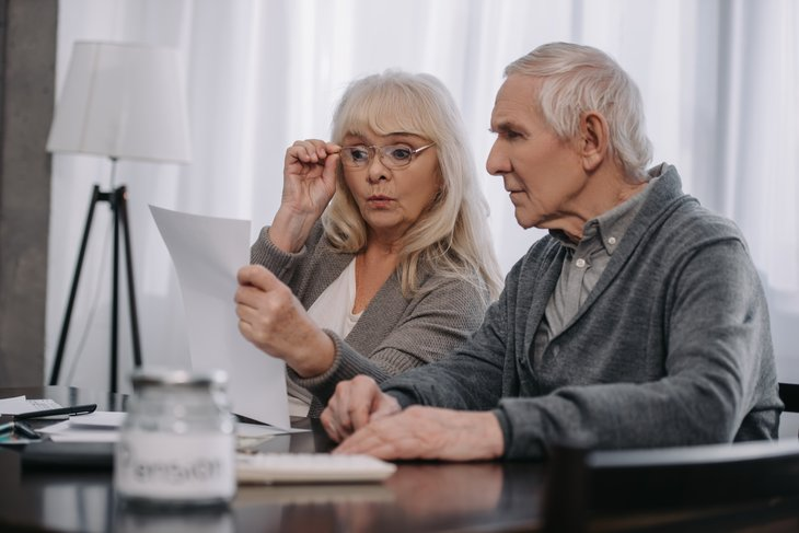 A surprised senior couple looks at a document