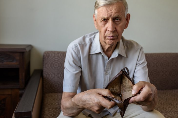 Older man holding an empty wallet