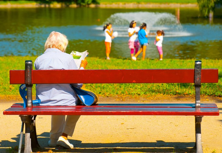Old woman sitting on bench in park
