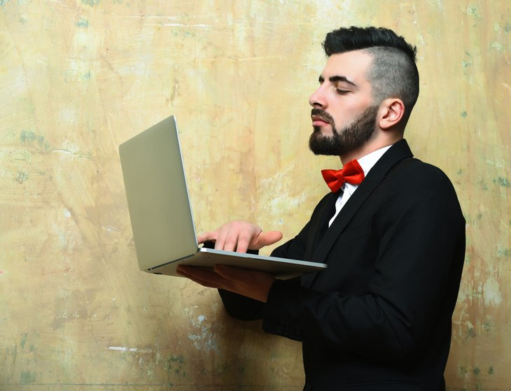 Young hip white businessman beard, stylish haircut holding laptop