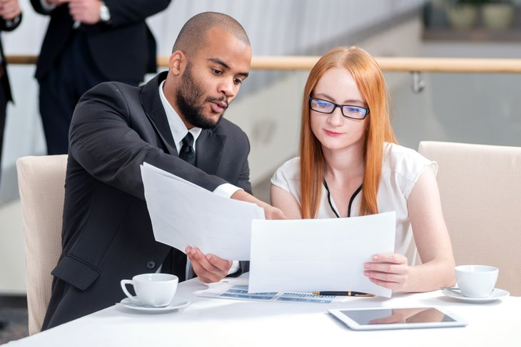 Young businessman business woman talking discussing documents table holding papers
