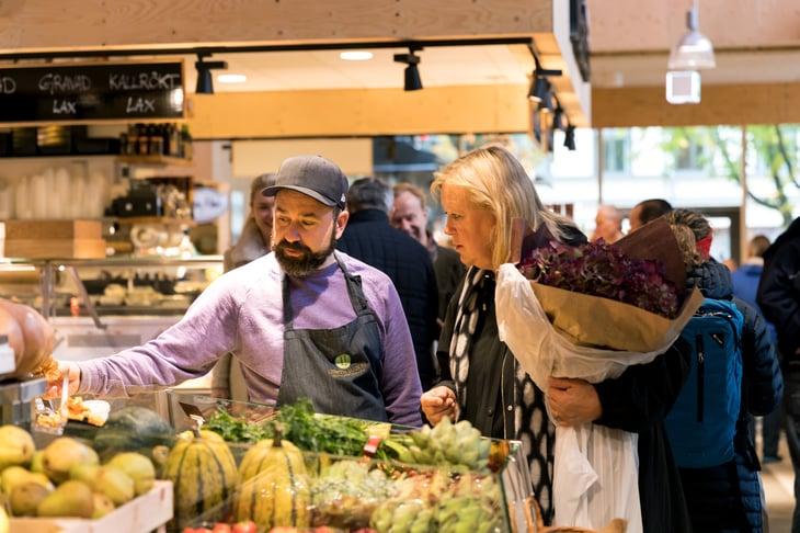 food market Ostermalmtorg in Stockholm, Sweden. Woman and farm seller