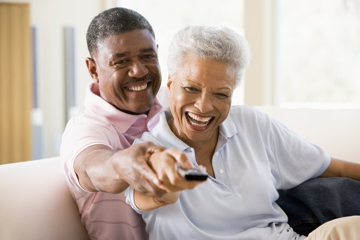 Couple in living room using remote control