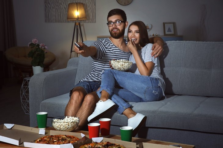 Couple watches TV on couch