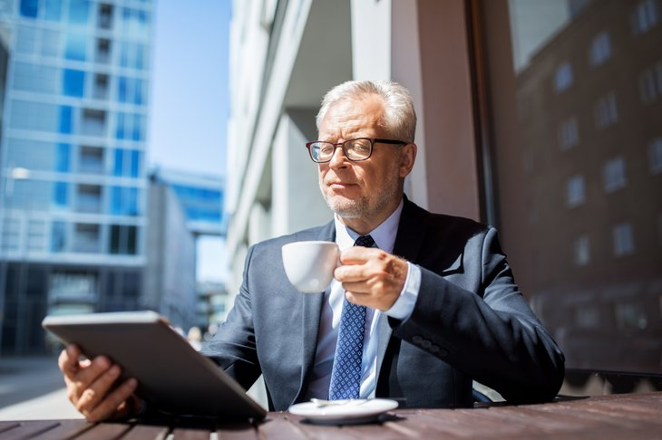 Businessman with tablet PC drinking coffee