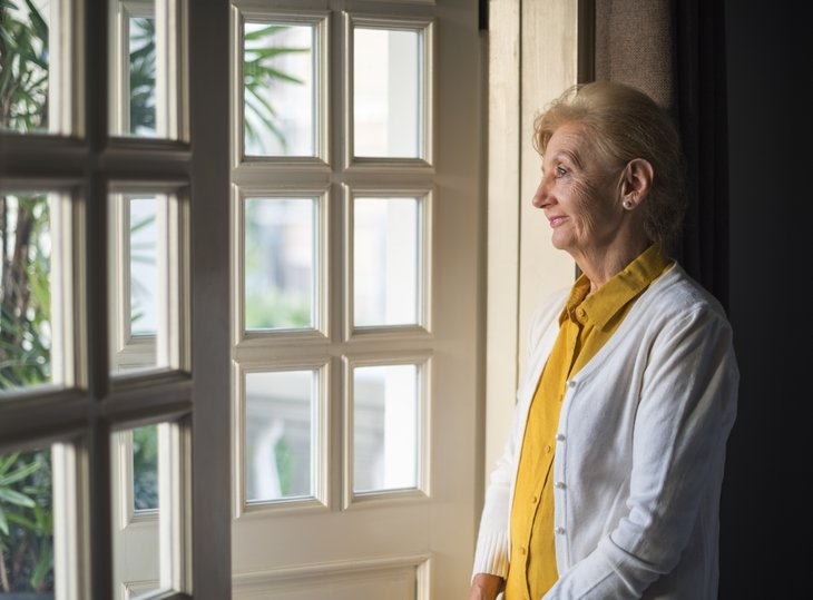 A senior woman looks out the window of her home