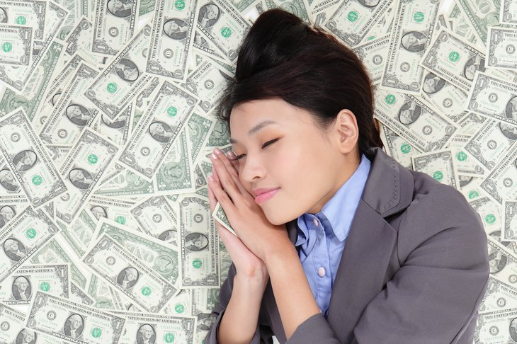 Young woman sleeping on money
