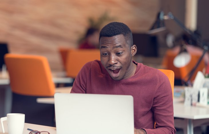 A happy worker is surprised at his desk while on a laptop computer