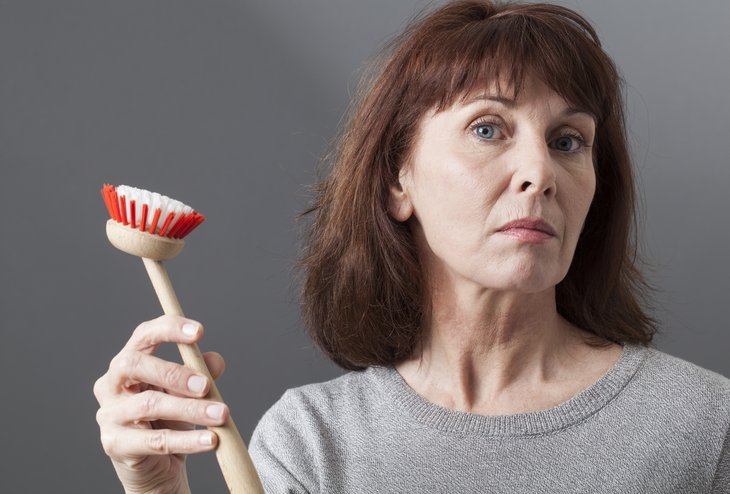 Skeptical woman with cleaning brush
