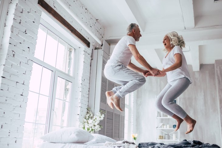 Couple jumping on bed, holding hands