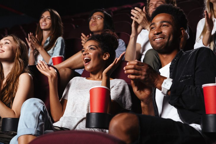 Multiethnic movie happy audience clapping