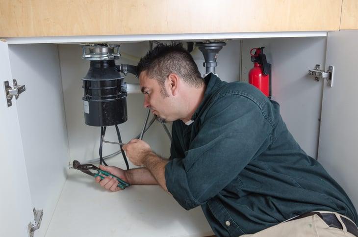 Plumber working on garbage disposal