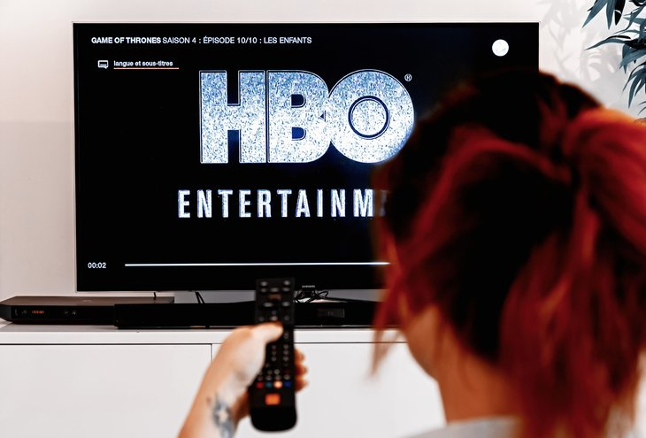 A woman holds a TV remote control while watching HBO