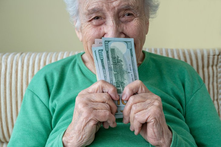 A happy senior holds $100 banknotes