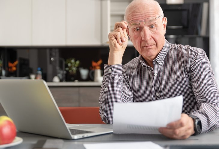A senior lifts his eyeglasses in surprise at a bill while working at his kitchen table with a laptop computer
